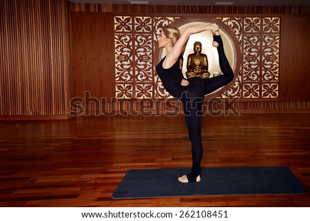Beautiful young sexy blond girl with a sporty physique slender figure doing yoga exercises  fitness in slinky suit meditates relaxes pilates  - stock photo