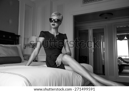 Beautiful young sexy blond woman with short hair sunglasses  makeup business woman reading a rest in a room  in the luxurious interior in stylish clothes collection