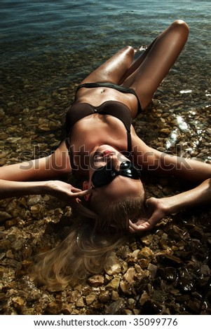 Beautiful young sexy blonde wearing sunglasses, laying in water - stock photo