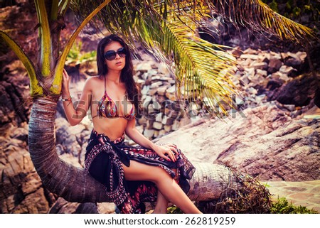 Beautiful young sexy girl is sitting on a palm tree - stock photo