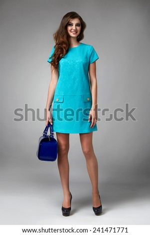 Beautiful young sexy girl with long wavy blond hair with a bright evening make-up perfect summer tan thin figure dressed in colored short dress and high heels shoes holding a small handbag - stock photo