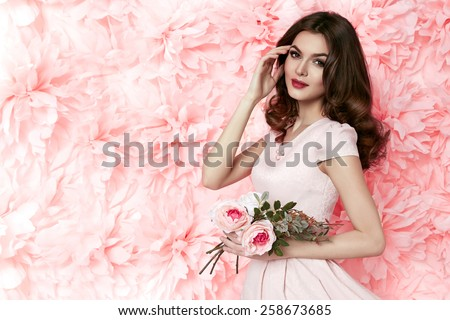 Beautiful young sexy girl with long wavy brunette hair with a bright evening make-up perfect summer tan thin figure dressed in colored short dress holding flower pink  - stock photo