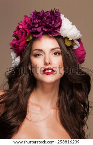 beautiful young sexy model with bright flowers on her head