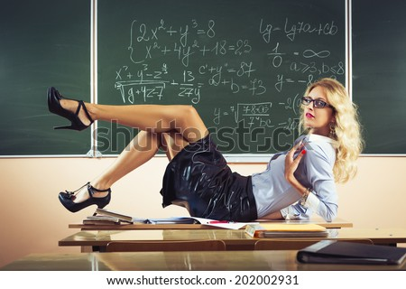 Beautiful young sexy teacher posing on table - stock photo