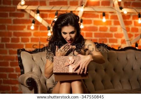 Beautiful young sexy woman holding present box - stock photo