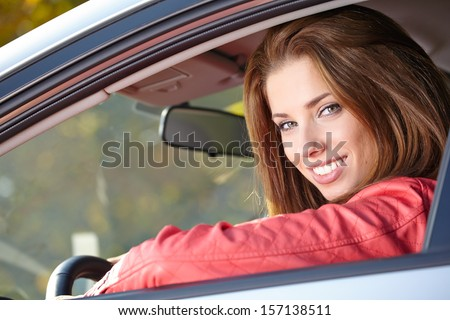 Beautiful young sexy woman in car looking from window on autumn background  - stock photo