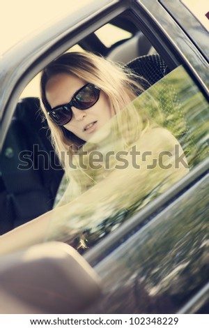 Beautiful young sexy woman in car looking from window on nature background.