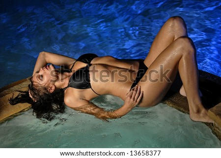 Beautiful young Sexy woman lying down on edge of Jacuzzi in pool