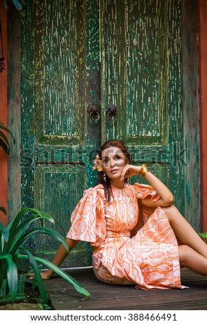 Beautiful young sexy woman model with perfect figure, bright makeup,  wearing orange dress with python pattern, in palm leaves in the jungle, shadows, shining sun, free place for text. Fashion photo