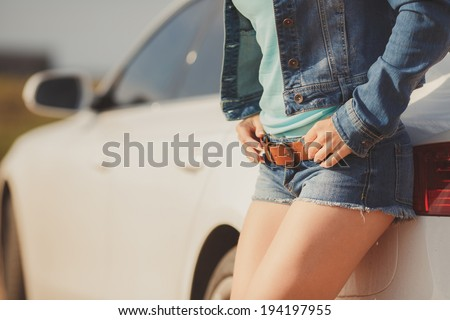 Beautiful young sexy woman near car outdoor. Rich hot blond slim girl with long healthy hair posing with luxury expensive automobile. Fashion model spring-summer - stock photo