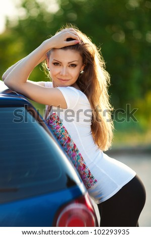 Beautiful young sexy woman standing near a car outdoor - stock photo