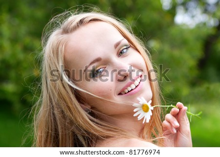 beautiful young sexy woman with chamomile, summer day