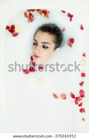 Beautiful young sexy woman with dark hair wet and makeup in milk bath. Wellness  and SPA in beauty cosmetic salon. Romantic atmosphere for woman at Valentine's Day. Selective focus. Copy space. - stock photo