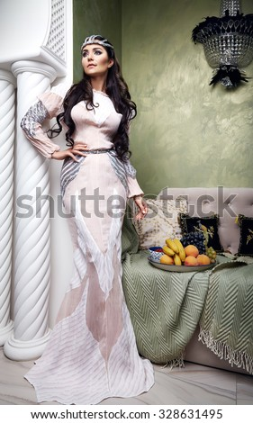 Beautiful young sexy woman with long dark hair brunette and decoration in evening dress of silk lace, room bedroom in Moroccan style velvet pillows luxurious furniture fashion harem concubine fruit - stock photo