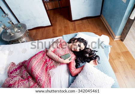 Beautiful young sexy woman with long dark hair brunette and decoration in evening dress of silk lace, room bedroom in Moroccan style velvet pillows luxurious furniture fashion harem concubine bed - stock photo