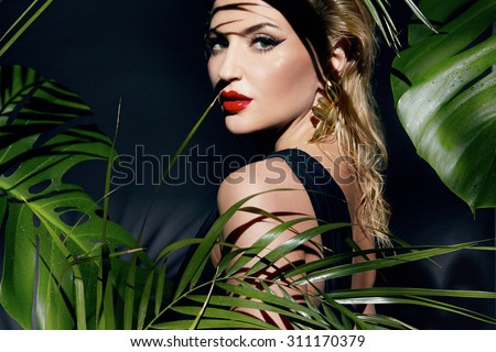 Beautiful young sexy young woman model with perfect figure and tanned skin body bright makeup oil and water drops on the hand wearing lots of bracelet palm leaves in the jungle shadows shining sun - stock photo