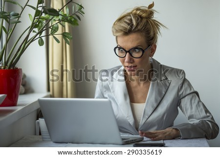 Beautiful young shocked business woman sitting in front of laptop computer looking at screen. Emotionally expression face, feelings, problem, perception, reaction. - stock photo