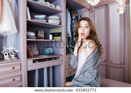 Beautiful young shocked woman don't know what to wear sitting in her closet - stock photo
