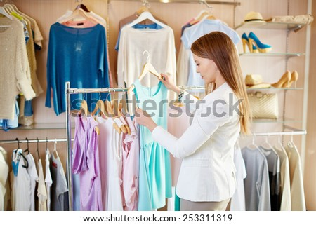 Beautiful young shopper choosing dress in boutique