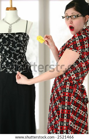 Beautiful young shopper shocked by dress price tag. - stock photo