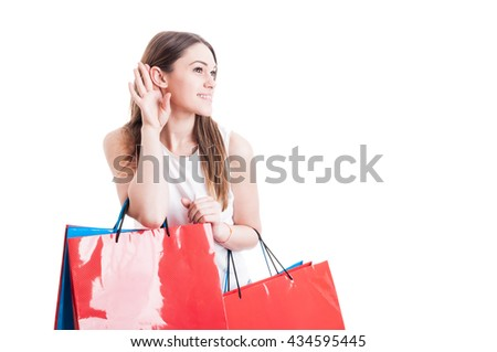 Beautiful young shopper with paper bags listening gossip and doing shopping isolated on white background with advertising area