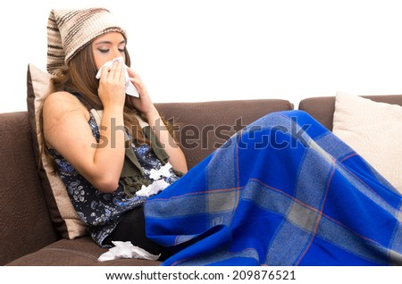 Beautiful young sick girl with the flu blowing her nose - stock photo
