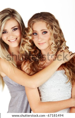 beautiful young sisters with long blond hair smiling in party dresses - not isolated - stock photo