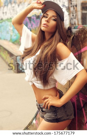 Beautiful young skater girl posing in t-shirt and sexy shorts. Outdoor fashion portrait. - stock photo