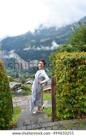 Beautiful young, slim, short-haired caucasian woman standing in a long dress on the mountain background. Travel concept. Freedom concept. Swiss Alps