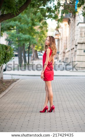 Beautiful young slim woman in a street of European city, business lady in red dress and high heels.