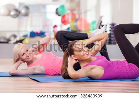 Beautiful young slim women are doing exercise in gym. They are lying on carpers and stretching legs up. The ladies are looking forward and laughing - stock photo
