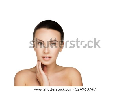 beautiful young smiling brunette woman with clean fresh skin with nude makeup touching herself by hand. Closeup real photo - stock photo