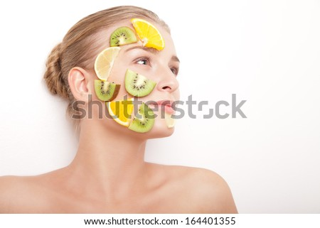 Beautiful young smiling cheerful woman with fruit mask on her face isolated on white background - stock photo
