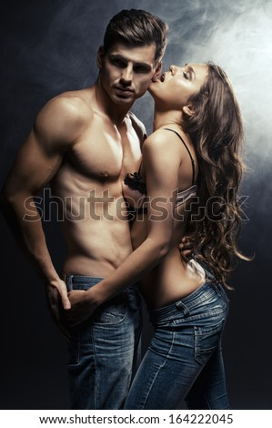 Beautiful young smiling couple in love embracing indoor