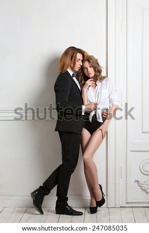 Beautiful young smiling couple in love embracing indoor. Beauty and Fashion. - stock photo