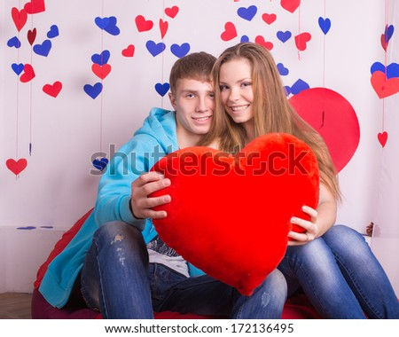 Beautiful young smiling couple with a gift in the form of heart - stock photo