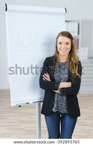 Beautiful young smiling female office worker with folded arms standing in front of word welcome written on large graph chart easel
