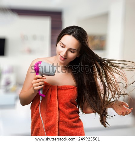 Beautiful young smiling long-haired woman wearing a towel drying hair in bathroom - stock photo