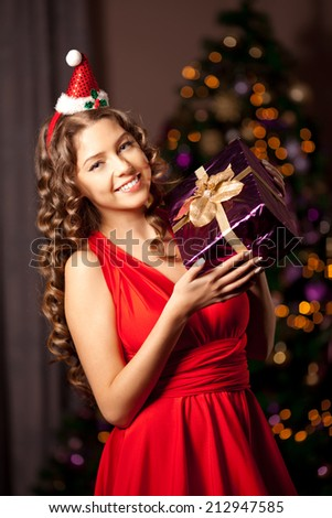 Beautiful young smiling santa girl. Luxury wealthy woman in the Christmas interior. At the Christmas tree.