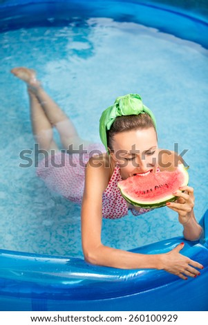 Beautiful young smiling woman in the pool with watermelon - stock photo