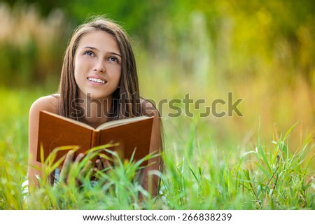 Beautiful young smiling woman lying on grass reading book, against green of summer park.
