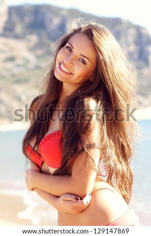 beautiful young smiling woman posing in red bikini at the beach - stock photo