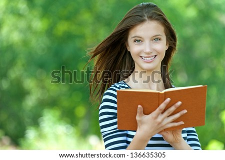 Beautiful young smiling woman reading book, against green of summer park. - stock photo
