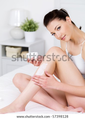 Beautiful young smiling woman sitting on a bed and applying cream on her attractive legs - vertical - stock photo