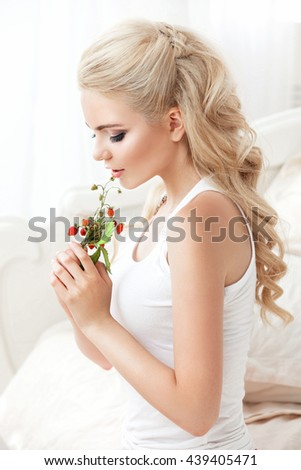 Beautiful young smiling woman sitting on white bed , holding a bunch of wild berries strawberries . Waking up in the morning. White hair color , shot in bright tone . Beauty girl face - stock photo
