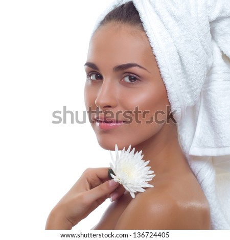 beautiful young smiling woman with a towel on his head and a flower in her hand on a white background.Clear skin.Spa. - stock photo