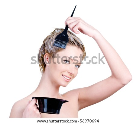 Beautiful young smiling woman with brush and capacity for hair-dye coloring her hair - white background - stock photo