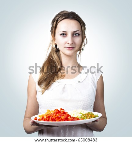beautiful young smiling woman with dish of vegetables - stock photo