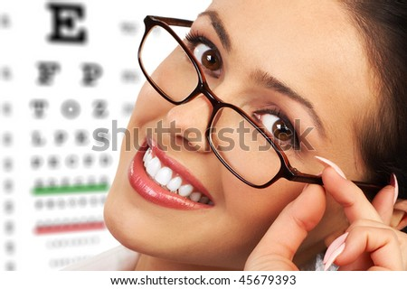 Beautiful young smiling woman with eyeglasses and eye chart