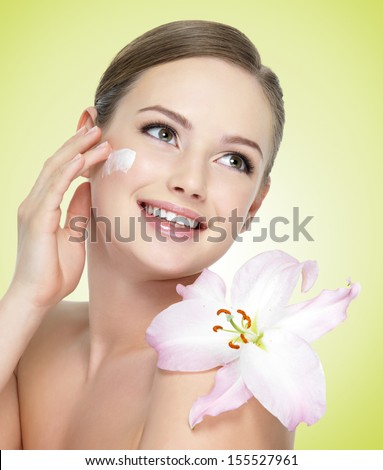 Beautiful young smiling woman with flower  applying cosmetic  cream on  face
